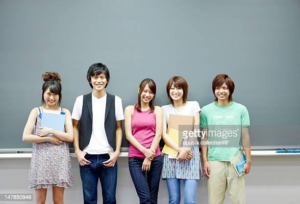 Five students in front of blackboard