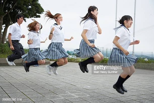 Five students (15-18) in school uniforms jumping in midair, side view