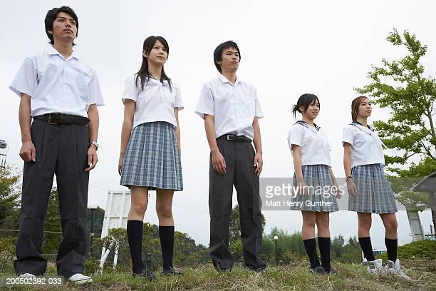 Five students (15-18) in school uniforms standing in row