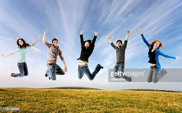 Five students jumping, outdoors
