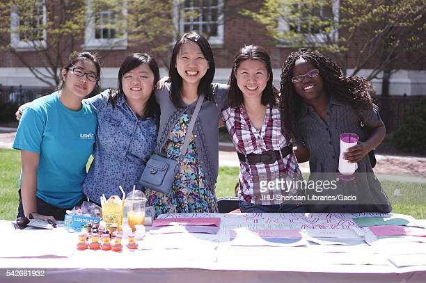 Five students smiling pose for photograph with arms together manning a table about Asian trivia during Spring Fair a studentrun spring carnival at...