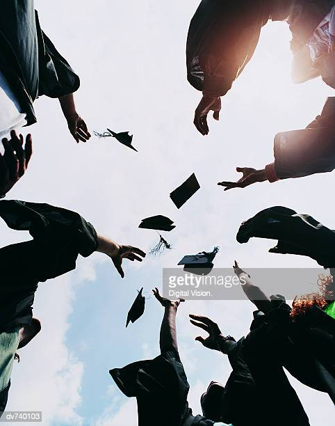 five students throwing their mortar boards in the air at graduation - graduation cap stock pictures, royalty-free photos & images