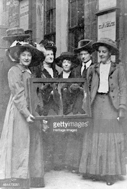 Five suffragettes holding a broken window in its frame 1912 Adela Pankhurst is on the far left From 1911 window smashing as executed by Mary Leigh...