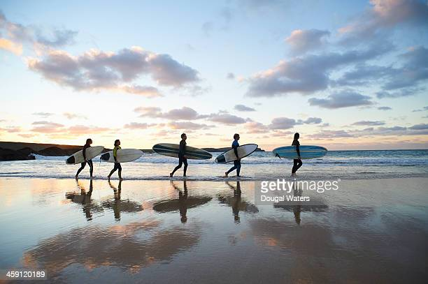 five surfers walk along beach with surf boards. - cinco personas fotografías e imágenes de stock