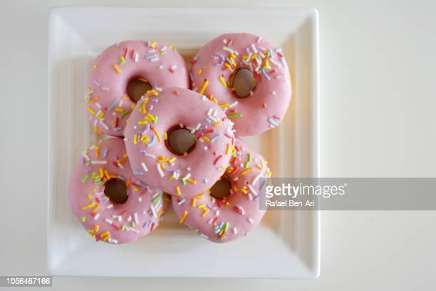 Five Sweet Pink Donuts Served on a Square White Plate