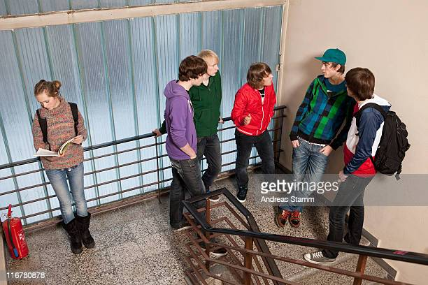 Five teenage boys talking and ignoring a teenage girl in a school stairwell