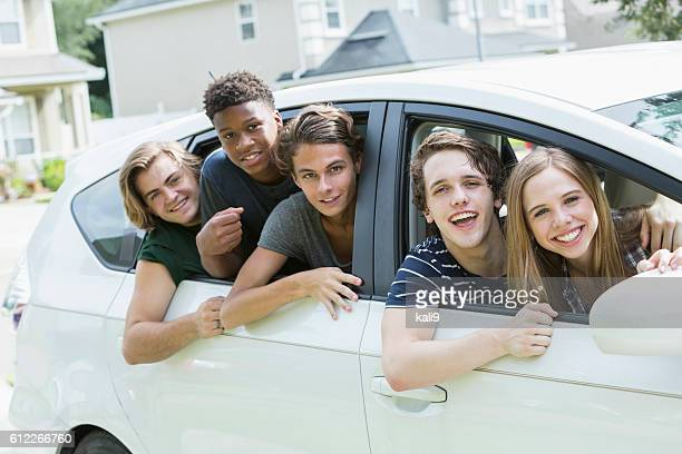 Five teenage friends leaning out car windows