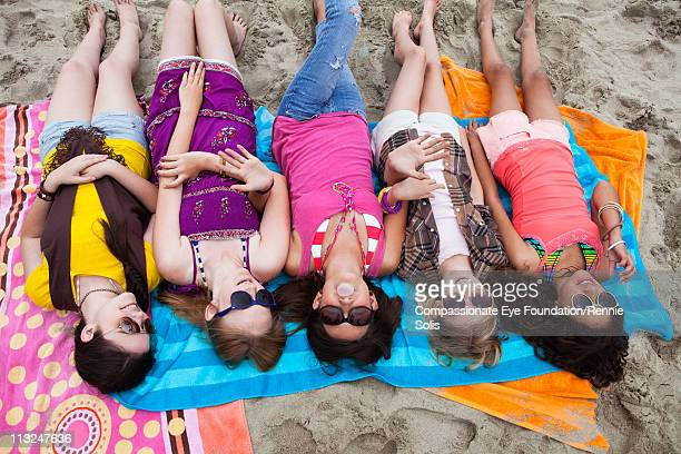 Five teenage girls lying on the beach