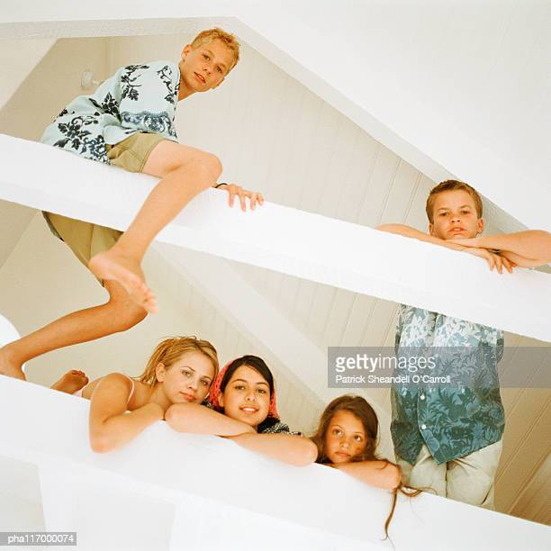 Five teenagers in loft looking into camera, low angle view
