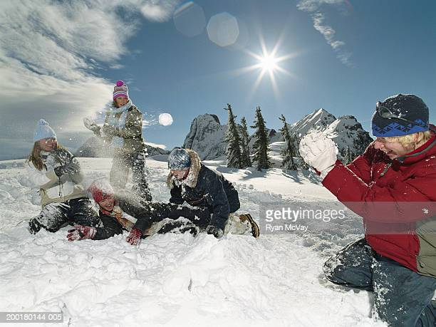 Five teenagers (15-18) throwing snowballs at one another, laughing
