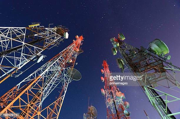 five telecommunication towers under a night sky  - telecommunications equipment stock photos and pictures