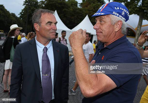 Five time winner of the Tour de France Bernard Hinault chats with three time winner of the Tour Greg LeMond of USA following the twenty one and last...