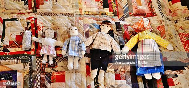 Five Toy Dolls On Patchwork Quilt