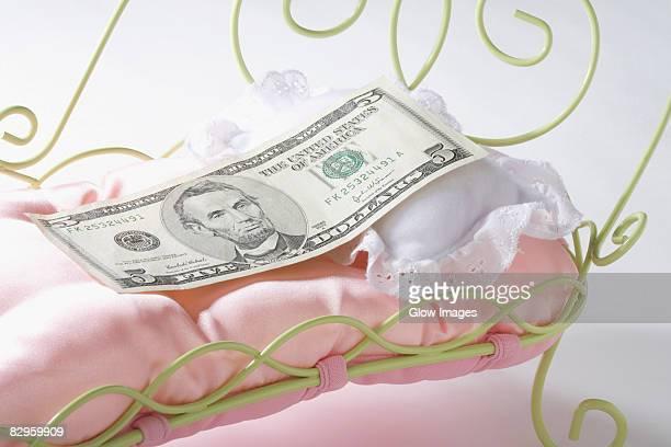 Five US dollar bill on a miniature bed