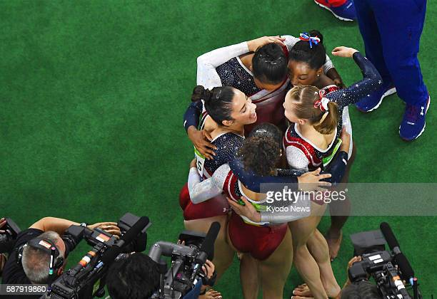 Five US gymnasts hug in a ring of joy after winning gold in the women's team competition at the Rio de Janeiro Olympics on Aug 9 2016 The US team led...