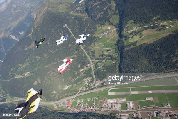 five wingsuiters fly in formation - five people stock pictures, royalty-free photos & images