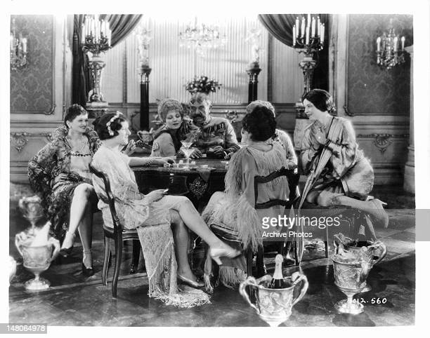 Five women dressed as flappers sit around a table laughing in a scene from the film 'The Wedding March' 1928