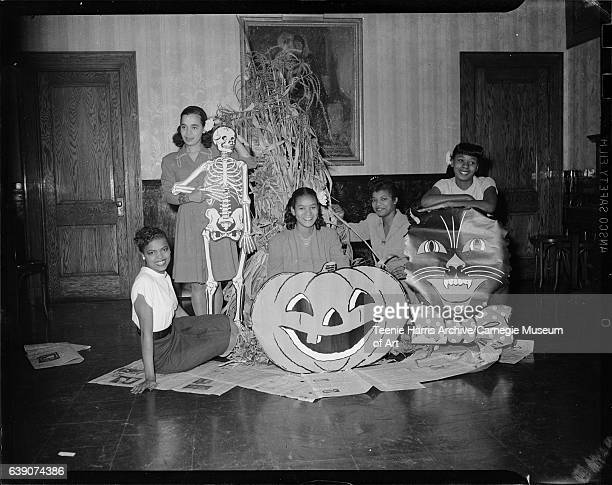 Five women including Doris Harper second from right posed with Halloween decorations including corn shock jackolantern black cat and skeleton in room...