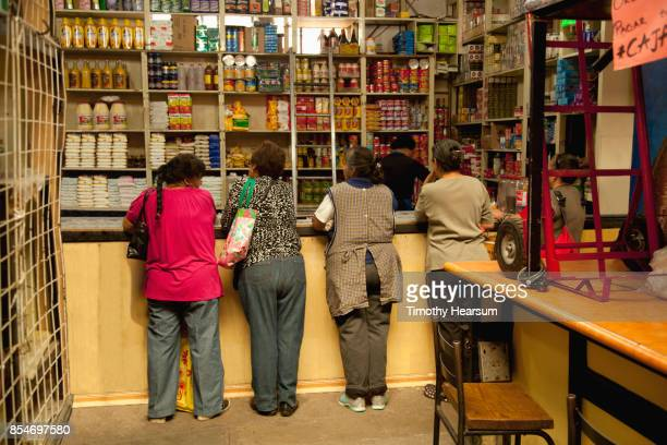 five women lean on a counter as a clerk pulls their orders from well stocked shelves - timothy hearsum imagens e fotografias de stock