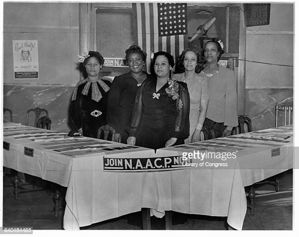 Five women, members of the Planning Committee for the National Association for the Advancement of Colored People, stand by tables loaded with...