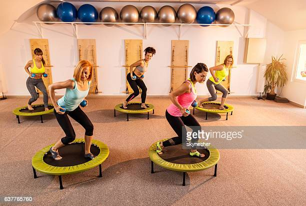 Five women on mini trampolines exercising with Pilates weight balls.