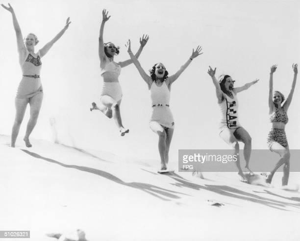 Five women romp gaily on a sand dune on an English beach, circa 1935.
