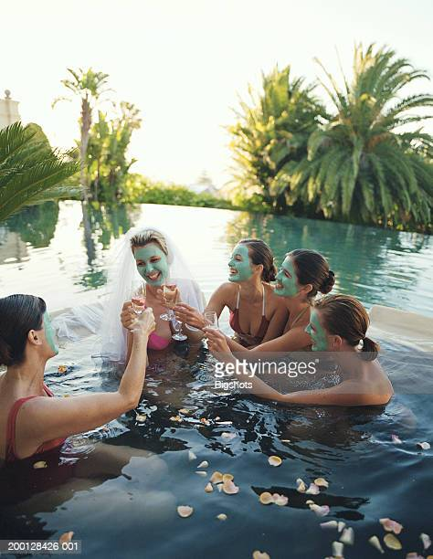 Five women wearing face masks in hot tub, one wearing bridal veil