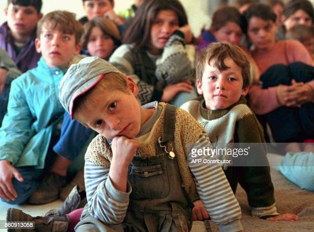 Five year old Albanian refugee boy Nebi looks on as he takes shelter with other ethnic Albanian children in a school in the village of Tushila near...