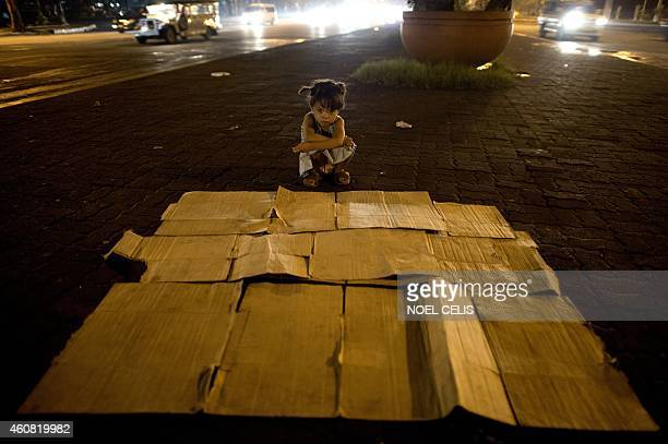 Five year old Angela Cruz prepares her bed made of paperboard along a street in Manila on December 24 2014 The Philippines is the largest Christian...