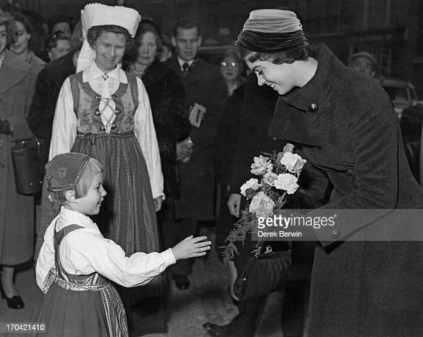 Five year old Ann Evander presents a bouquet to Princess Margaretha of Sweden as she attends the opening of the Christmas Fair at the Swedish Church...