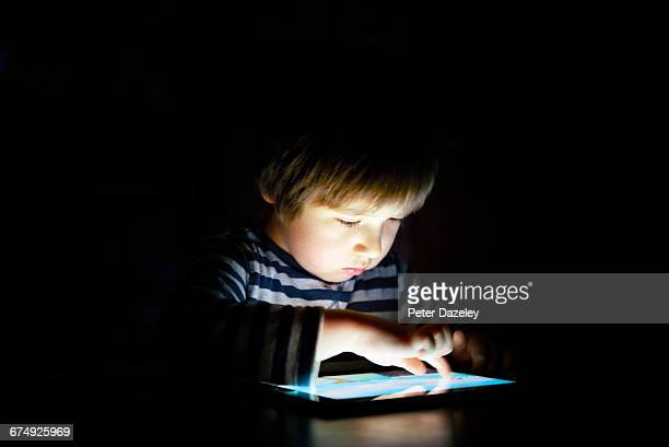 Five year old boy on digital tablet at night