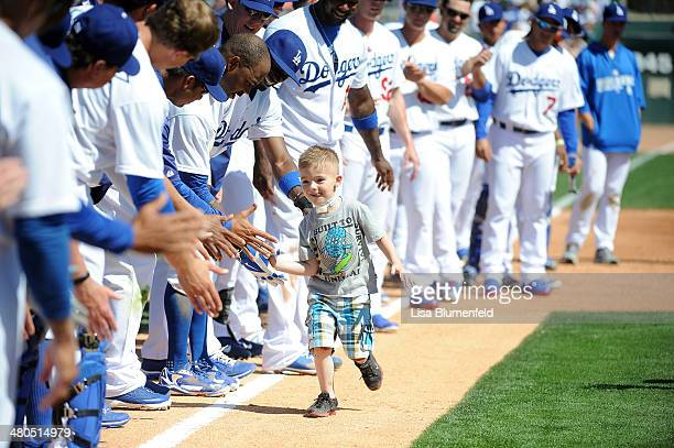 Five year old Cash Davis runs the bases and high fives the Los Angeles Dodgers during the game against the San Diego Padres at Camelback Ranch on...