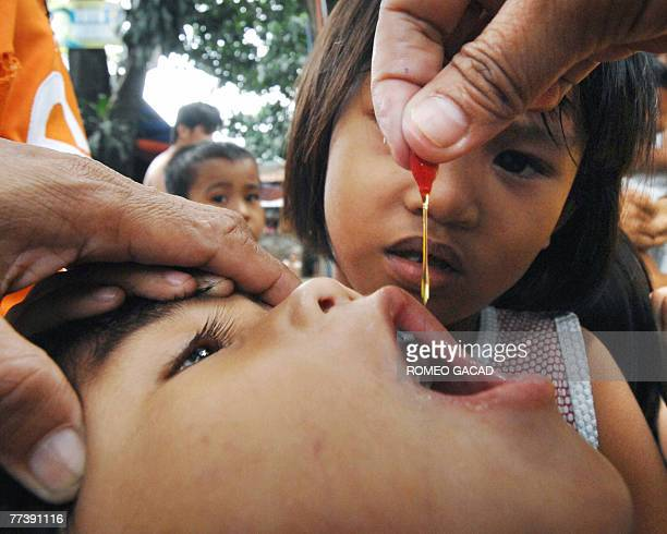 Five year old Gernalyn Aresgado receives vitamin A drops that will benefit eyesight after receiving a shot of antimeasle vaccine during a house to...