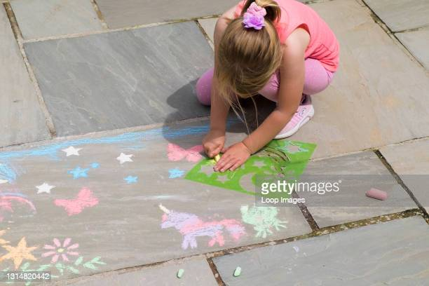 Five year old girl amusing herself busily using plastic stencils to chalk shapes on a flagstone floor.