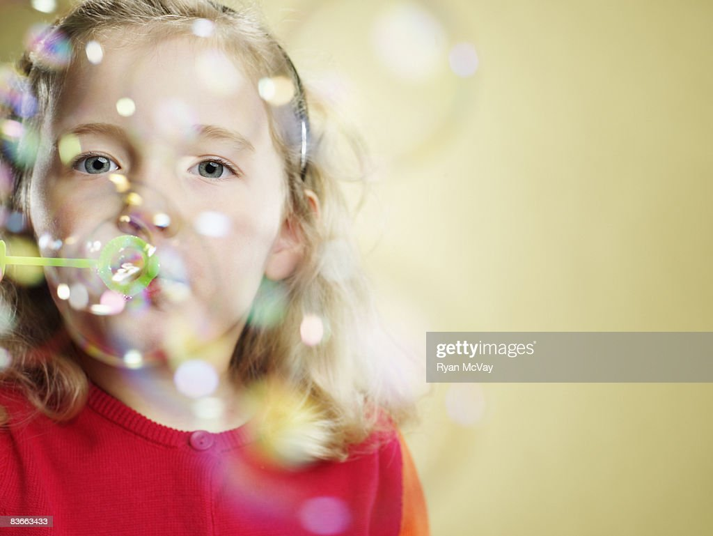 Five year old girl blowing bubbles.  : Stock Photo
