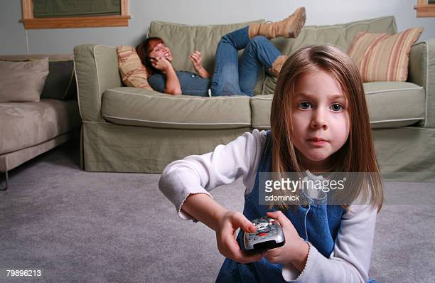 A five year old girl changing TV channels while her babysitter/young mother ignores her in the background.