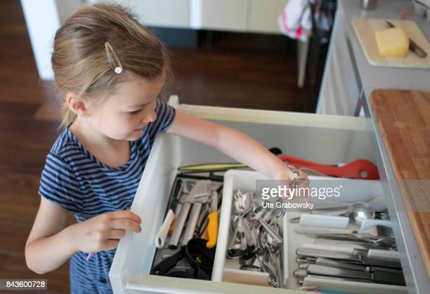 A five year old girl helps to cover the table and takes cutlery from a drawer on August 07 2017 in Bonn Germany