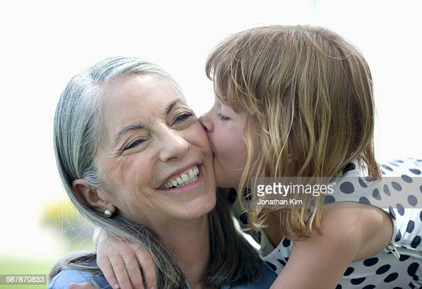 Five year old girl kisses her grandmother