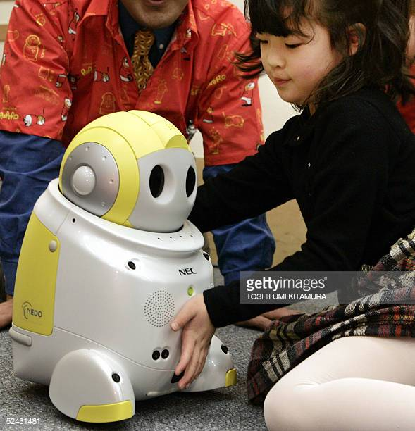 "Five year old Kanon Hiroi plays with NEC's new child-care robots, ""PaPeRo"", during its press preview in Tokyo, 16 March 2005. The 38.5cm-tall..."