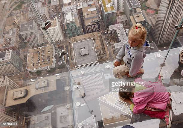 Five yearold Anna Kane and fouryearold Sophie Allaway check out the view from the Ledge a new glass cube that juts out from the 103rd floor Skydeck...