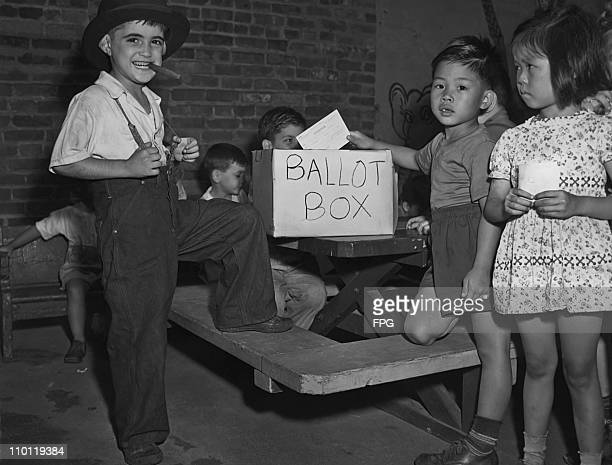 Five yearold Sam Yee casts his vote in a mock election at the Children's Aid Society in New York City August 1946 On the left is candidate Vito de...