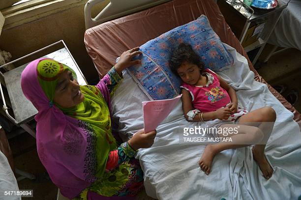 Five yearold Zohra Zahoor who has pellet wounds in her legs forehead and abdomen sleeps on a hospital bed as her aunt Naseema Jan looks on at a...