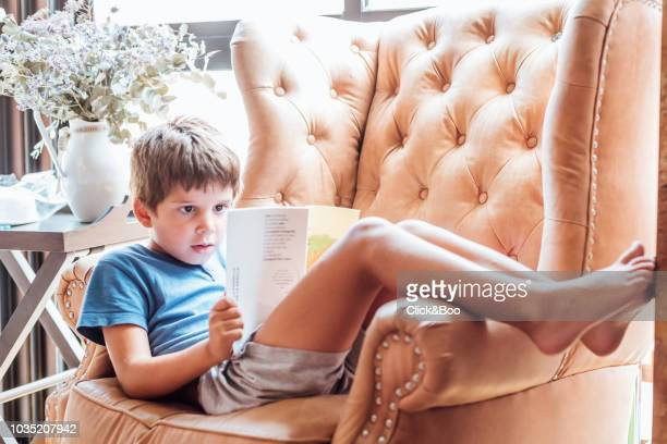 five years old kid reading a book sitting in a wing chair(home interior) - 4 5 years stock pictures, royalty-free photos & images