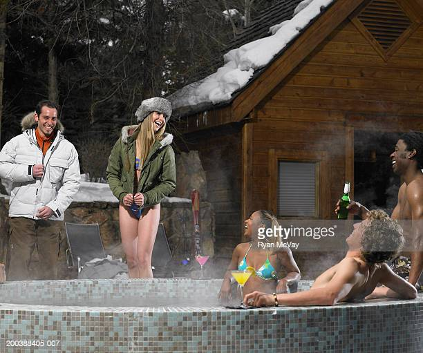 Five young adults drinking alcohol and soaking in hot tub, winter