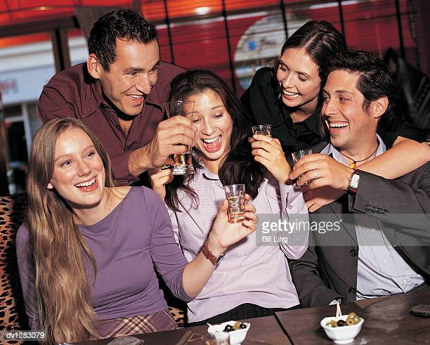 Five Young Adults Enjoying their Drinks in a Bar