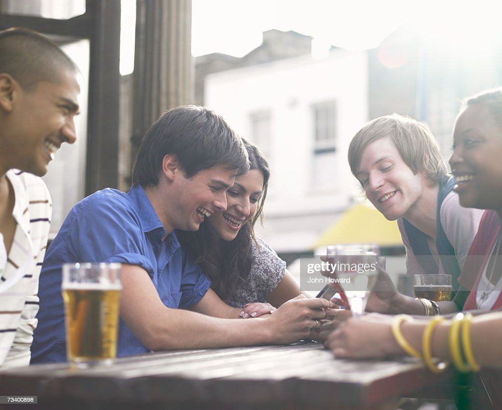 Five young adults sitting at outdoor pub table, man with mobile phone : Foto de stock