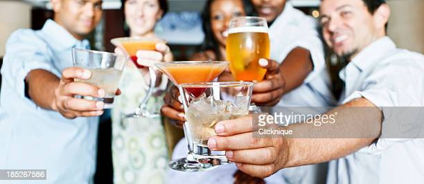 Five young adults socializing in a hotel bar over drinks