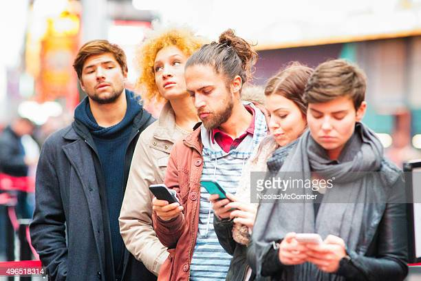 Five young adults waiting in line some using phones