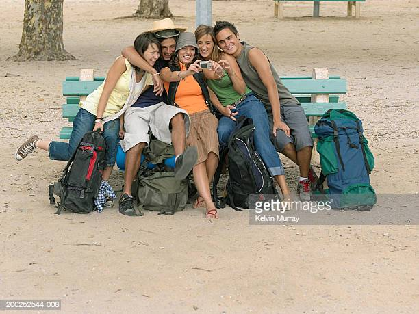 Five young backpackers on bench taking photo of themselves, smiling
