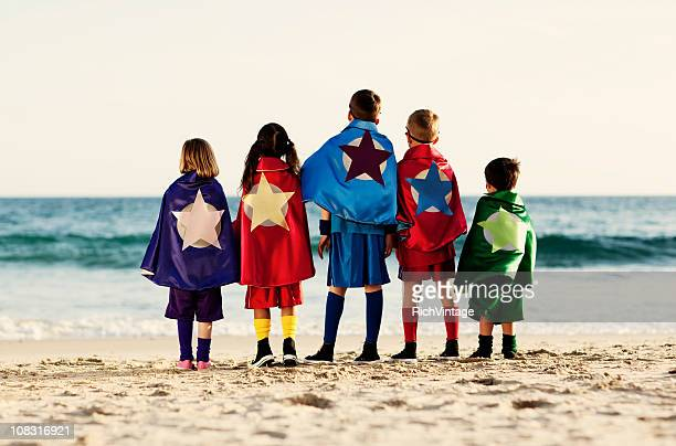 five young children dressed as superheroes on beach - five people stock pictures, royalty-free photos & images